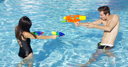 Happy young male and female couple shooting off colorful plastic water guns at each other in swimming pool
