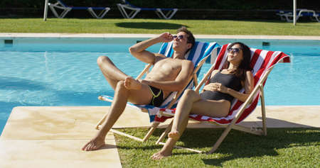 diverse: Young couple relaxing at a resort swimming pool sitting sunbathing on colorful deck chairs as they enjoy the hot summer sun on vacation