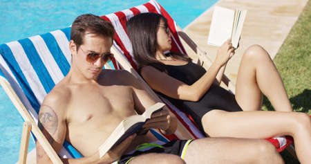 mixed marriage: Relaxed attractive young couple reading poolside reclining in two colorful deck chairs on the lawn at the edge of the water in the summer sun