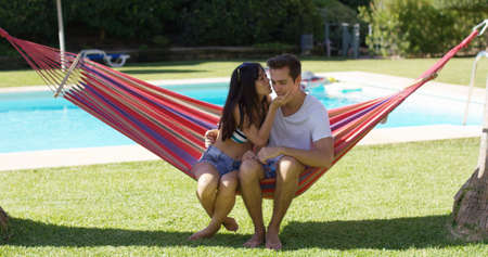 Loving couple in hammock kissing each other with swimming pool behind them during summer