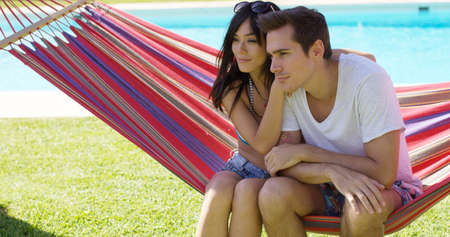 mixed marriage: Affectionate young couple sitting on a colorful stripes hammock in the shade of a tree at the side of a swimming pool watching something intently off screen. Stock Photo