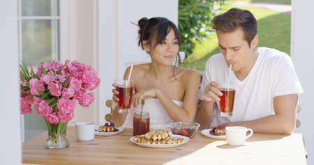 tea table: Young attractive couple drinking iced tea together at table with breakfast waffles  coffee  fruit and pink flower vase