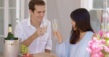 mixed marriage: Young happy adult couple toasting champagne glasses in celebration of something important