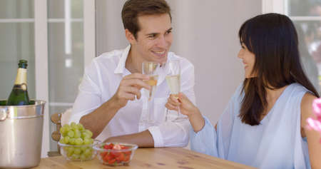 mixed marriage: Cheerful grinning adult couple toasting champagne glasses in celebration of something at table with fruit bowls