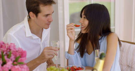 mixed race couple: Close up of attractive mixed race couple with happy expressions sipping wine and eating fruit