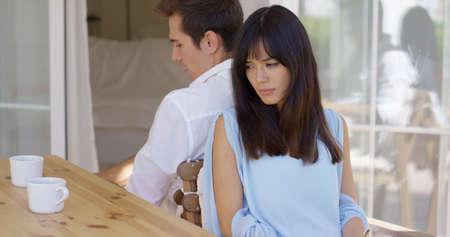 novios enojados: Enojado joven pareja mixta caucásica y asiática sentada de espaldas a la mesa después de tener una discusión o desacuerdo