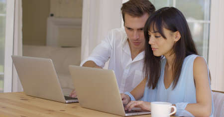 Man and woman at wooden table working on laptop computers together as they collaborate on a project online