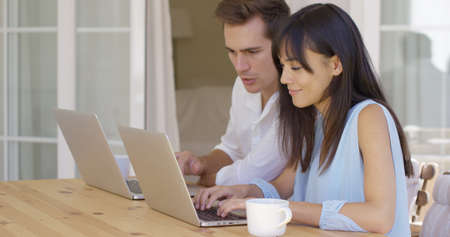 Attractive young man and woman at wooden table working on laptop computers together as they collaborate on a project or browse the internet wirelessly