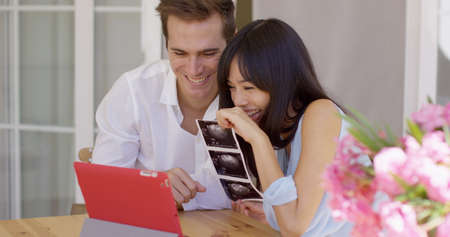 Happy young adult man and woman showing off ultrasound pictures of baby in womb to someone through a video chat on their tablet computer Stockfoto