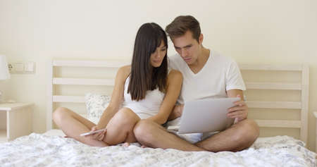mixed marriage: Young couple sitting together in underclothes while on bed while doing research on a laptop computer and smart phone