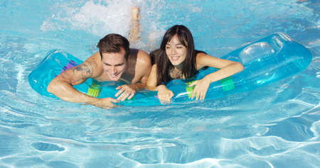 floating on water: Pair of joyful male and female adults swimming together on inflatable floating plastic mattress in outdoor pool Stock Photo