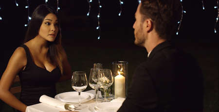 candle light dinner: Surprised woman looks questioningly at husband across restaurant dinner table at night