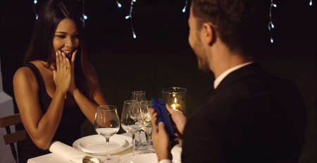 upmarket: Young woman overcome when presented with a gift on a romantic night out with a beau at an upmarket restaurant Stock Photo