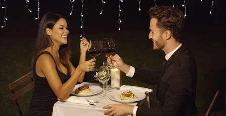 幸せなカップルは、彼らは彼らの愛を祝うロマンチックな夕食時に互いを焼くことを愛する