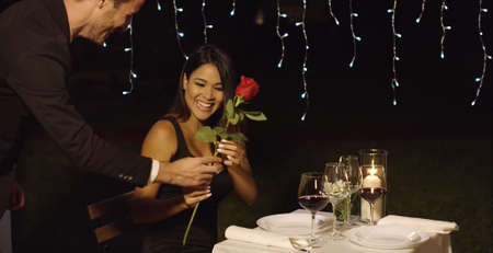 candle light dinner: Romantic man surprising his date with a red rose for Valentines or a special occasion as they dine out together at a luxury restaurant