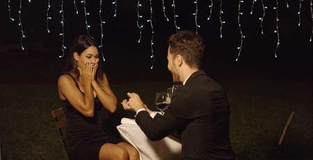 Geschokt elegante jonge vrouw die een huwelijksaanzoek van haar vriend in een chique restaurant omdat zij samen te genieten van een romantisch diner