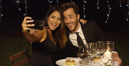 nighttime: Beautiful romantic couple enjoying an elegant dinner in a restaurant posing for a selfie smiling into the camera on their mobile phone