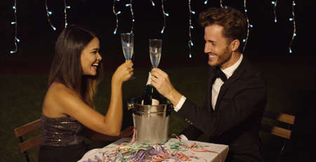 Happy New Year dinner celebration with a romantic elegant young couple toasting with flutes of champagne over a bottle in a cooler