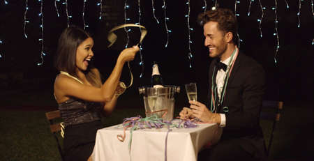 teases: Woman teases her dinner date with ribbon across table while sharing champagne