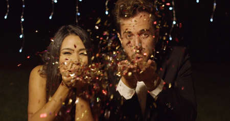 elegant party: Young couple celebrating New Year blowing colorful paper confetti over their hands towards the camera against twinkling party lights Stock Photo
