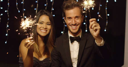 celebrate year: Elegant romantic young couple celebrating new year with sparklers laughing and smiling against a dark background with party lights Stock Photo