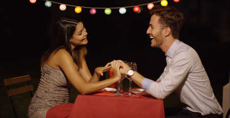 romantic man: Couple holds hands across table and smiles while casually dressed for a night time dinner date
