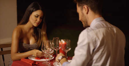 deep thought: Beautiful woman in deep thought across table from handsome dinner date at night Stock Photo