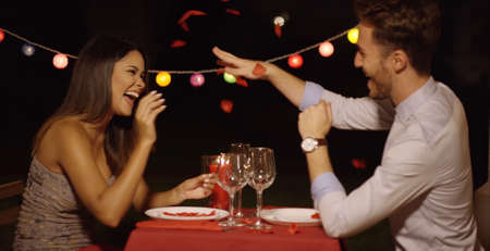 dinner date: Man makes flying gesture with right hand to make his dinner date laugh across red covered table Stock Photo