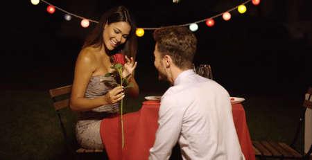 mujer sola: Hombre joven que da una hermosa mujer de un solo rojo rosa de tallo largo en el Día de San Valentín como una muestra de su amor