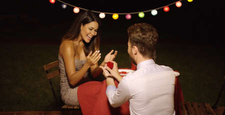 candle light dinner: Young man down on his knees proposing to his loved one offering her the ring in a box as she reacts with joyful surprise Stock Photo