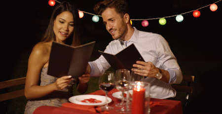 candle light dinner: Loving young couple choosing food off a menu as they enjoy a romantic dinner at a restaurant to celebrate Valentines Day