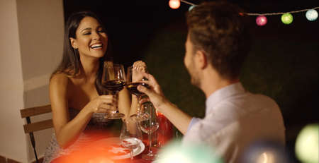 night shirt: Couple laughs as they raise their red wine glasses while on a night time date in fancy outdoor restaurant on Valentines day