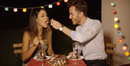 candle light dinner: Loving young man feeding his girlfriend a spoonful of cake as they celebrate Valentines Day together enjoying a romantic dinner with party lights