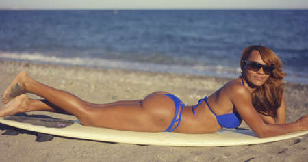 young black girl: Gorgeous young woman sunbathing in a bikini as she relaxes on a tropical beach lying on her surfboard at the edge of the ocean
