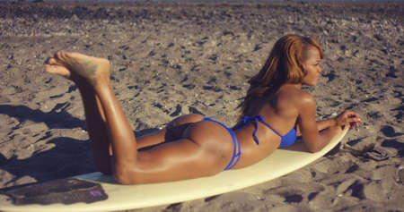 sun bathing: Sexy African Girl in Blue Bikini Looking at the Sea Waves While Lying on her Surfing Board and Sun Bathing at the Beach.