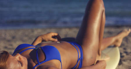 young black girl: Tanned woman in a sexy skimpy blue bikini lying on a surf board on the beach soaking up the summer sun  close up body view