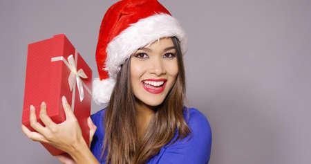 persona alegre: mujer joven magnífica excitado en un sombrero de Santa que sostiene un regalo rojo decorativo con arco como ella se ríe de la cámara sobre gris Foto de archivo