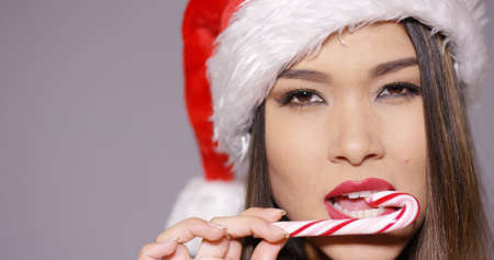 sultry: Sensual young woman in a festive red Santa hat biting a candy cane with a sultry seductive expression as she celebrates Christmas