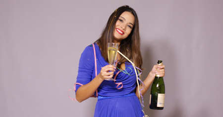 draped: Sexy young woman draped in party streamers standing with a bottle of champagne and flute of bubbly celebrating the New Year with a laugh Stock Photo