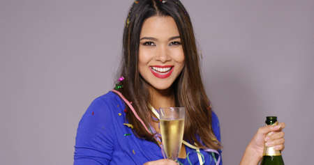 grins: Gorgeous young woman celebrating with champagne holding an opened bottle and full flute as she grins happily at the camera