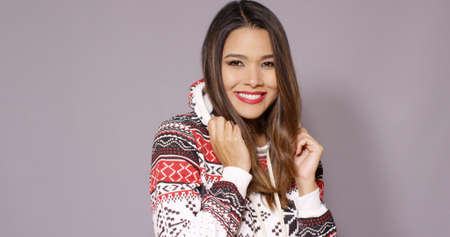 snuggling: Happy pretty woman in warm winter fashion snuggling into her cozy woollen jersey with an adorable smile  on grey
