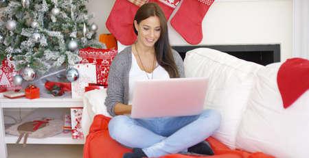 trabajando en casa: mujer joven sonriente contenta que trabaja en su computadora portátil mientras se relaja en las vacaciones de Navidad en su sala de estar de fiesta en su casa
