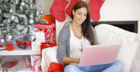 xmas tree: Contented smiling young woman working on her laptop while relaxing over the Christmas holiday in her festive living room at home