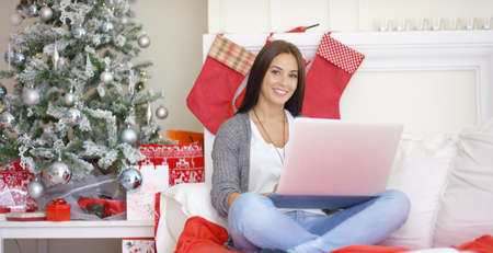 Contented smiling young woman working on her laptop while relaxing over the Christmas holiday in her festive living room at home