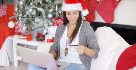shopping card: Happy young woman making online Christmas purchases using her laptop and credit card as she relaxes in a Santa hat in a festive red and white living room.