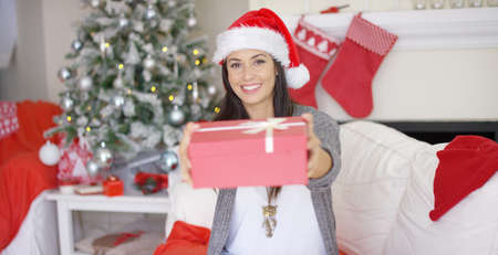 tied in: Laughing attractive young woman in a Santa hat offering a large Christmas gift tied in a bow to the camera in her festive decorated living room. Stock Photo