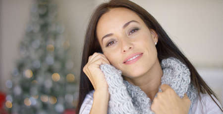 Dreamy young woman snuggling into her warm winter scarf as she relaxes at home during the holiday season in front of the Christmas tree