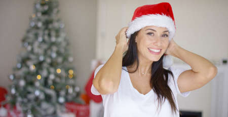 vivacious: Pretty vivacious woman donning a festive red Santa hat to celebrate Christmas in her decorated living room