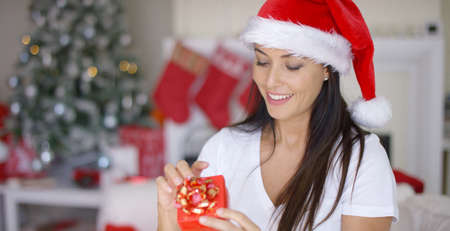 gleeful: Smiling woman unwrapping her Christmas gift with a look of gleeful anticipation as he celebrates Christmas at home in a red Santa hat Stock Photo