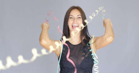 Vivacious laughing young woman in a black cocktail dress enjoying a party to celebrate the New Year over a grey background